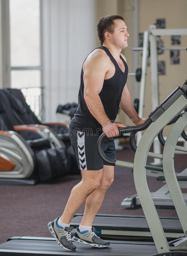 Athlete on the treadmill. Young athlete running at the gym on the treadmill stock image