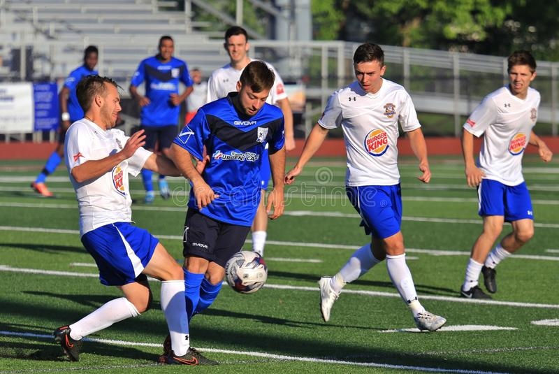 Athlete tries to evade the defended. Everyone congregates for the loose soccer ball at the professional Soccer event, pro football game, NPSL, National Premier stock images