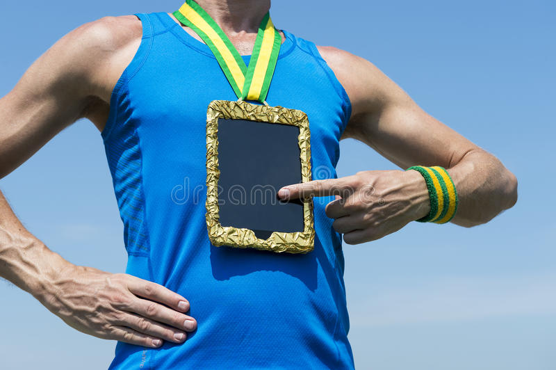 Athlete Using Gold Medal Tablet Computer. Athlete using tablet hanging as gold medal against blue sky stock photo