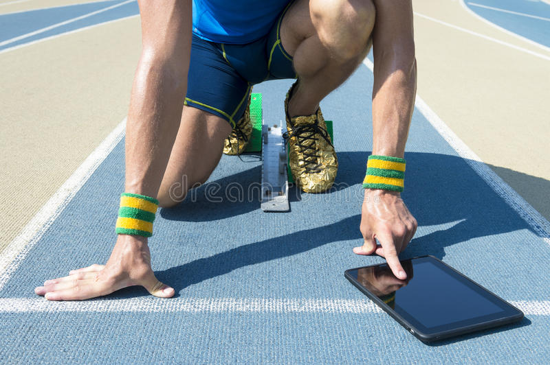 Athlete Using Tablet on the Track. Athlete crouching at the starting line of a running track wearing Brazil colors wristbands using his tablet stock photos