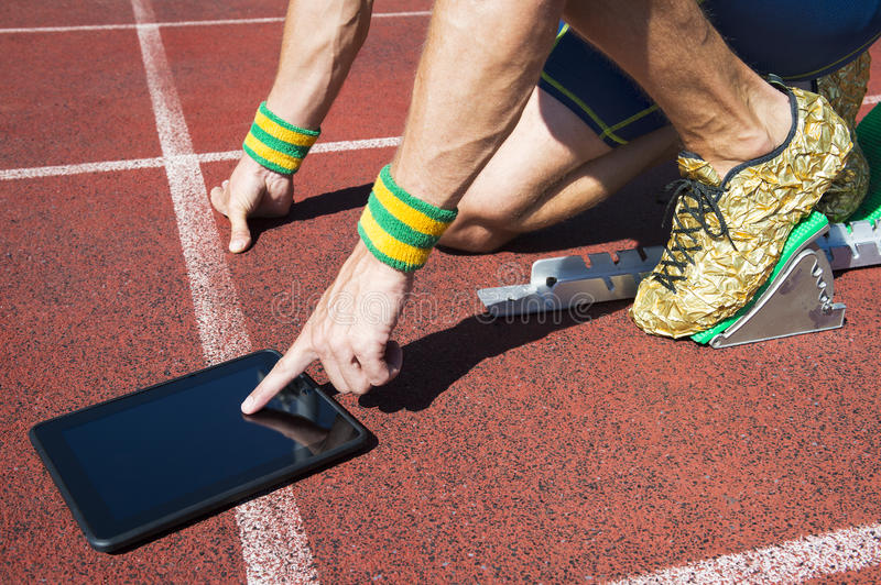 Athlete Using Tablet on the Track. Athlete in gold running shoes crouching at the starting line of a running track wearing Brazil colors wristbands using his royalty free stock photos