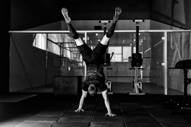 Athlete walking on his hands standing upside down in gym. Workout lifestyle concept.  Full body length portrait. stock photography