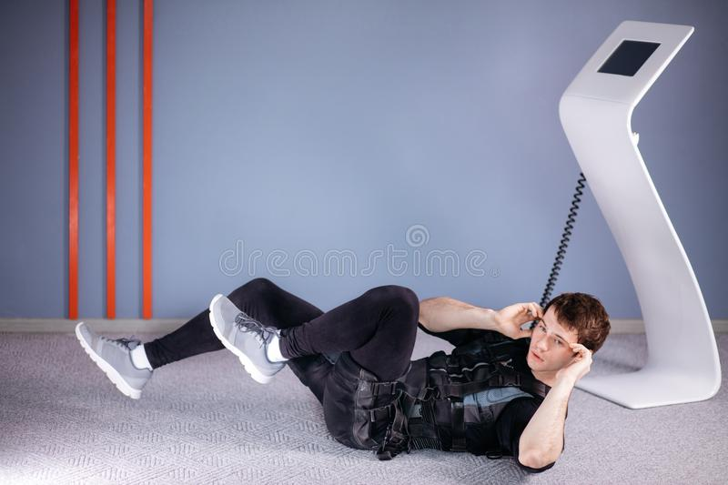 Athlete wearing ems suit doing abs exercise or sit ups royalty free stock image