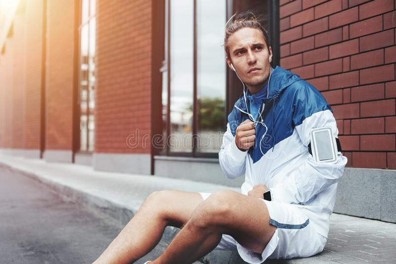 Young athlete in windrunner sitting on the street after good jogging session at sunset royalty free stock photo