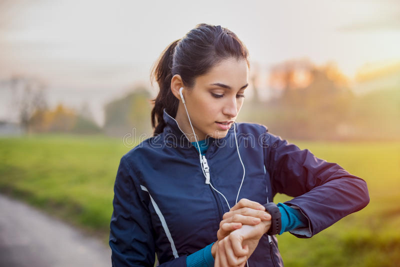 Athlete woman check smartwatch. Young athlete listening to music during workout at park and adjusting smart watch. Young latin woman setting smartwatch before royalty free stock image