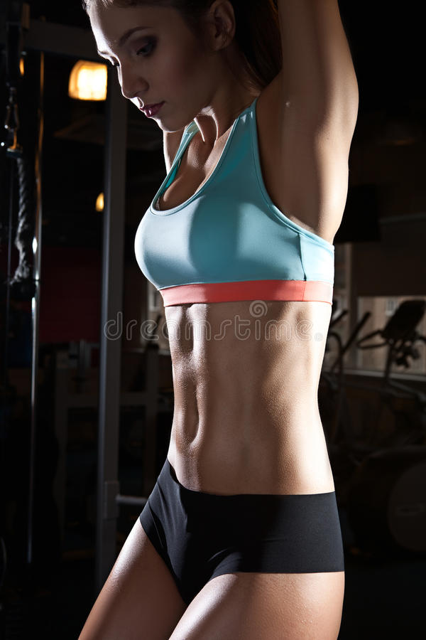 Athlete woman with perfect fitness body performing abdominal exercises stock images