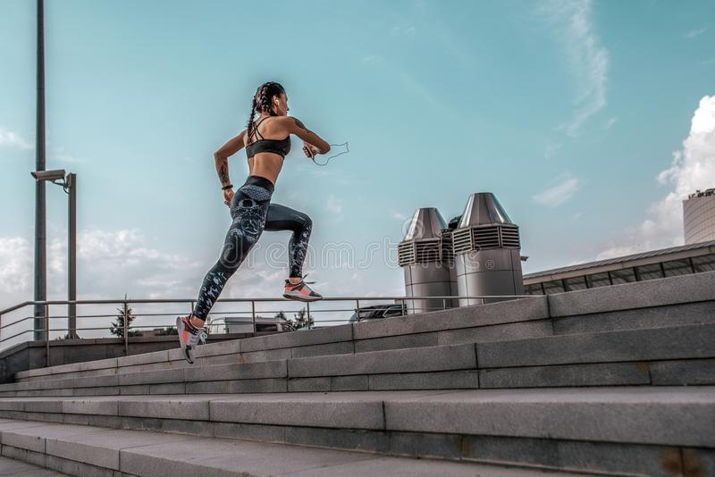 Athlete woman runs jump sports jogging training summer city. Headphones telephone. Concept fitness fresh air, active. Lifestyle workout. Free space. Background royalty free stock images
