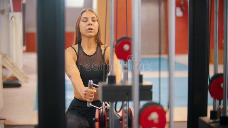An athlete woman training in the gym - pulling the handles connected to weight pieces. Mid shot stock image