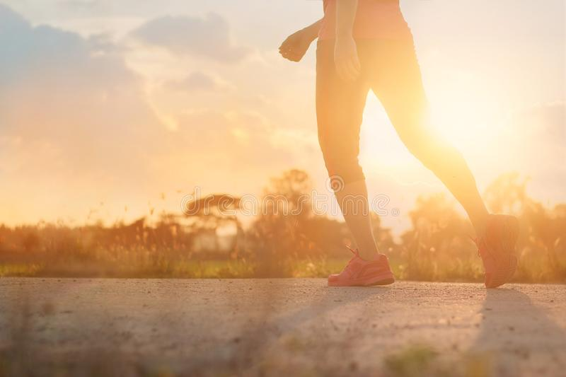 Athlete woman walking exercise on rural road in sunset background, healthy and lifestyle concept royalty free stock photo