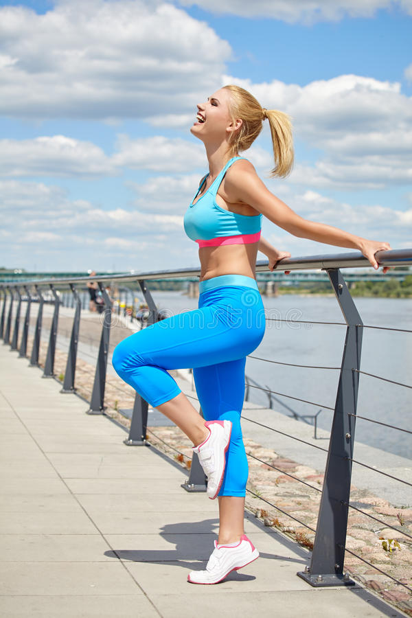 Athlete women's sportswear fit thin physique athletic build. Female athlete women's sportswear fit thin physique athletic build outdoor city river royalty free stock photos