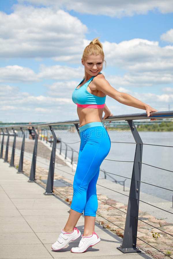Athlete women's sportswear fit thin physique athletic build. Female athlete women's sportswear fit thin physique athletic build outdoor city river royalty free stock image
