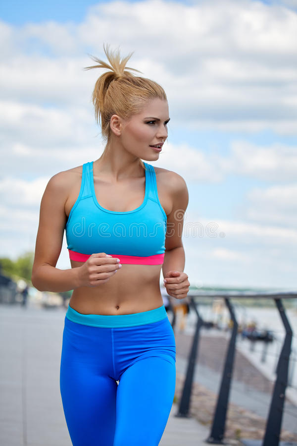 Athlete women's sportswear fit thin physique athletic build. Female athlete women's sportswear fit thin physique athletic build outdoor city river stock photo