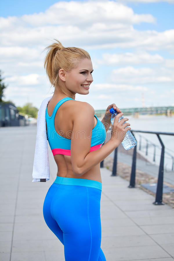 Athlete women's sportswear fit thin physique athletic build. Female athlete women's sportswear fit thin physique athletic build outdoor city river stock photography