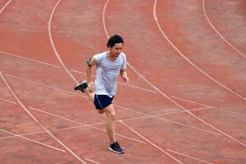 Athleten-Asian-Mann, der auf Rennbahn im Stadion läuft Gesundes aktives Lebensstil-Konzept stockfoto
