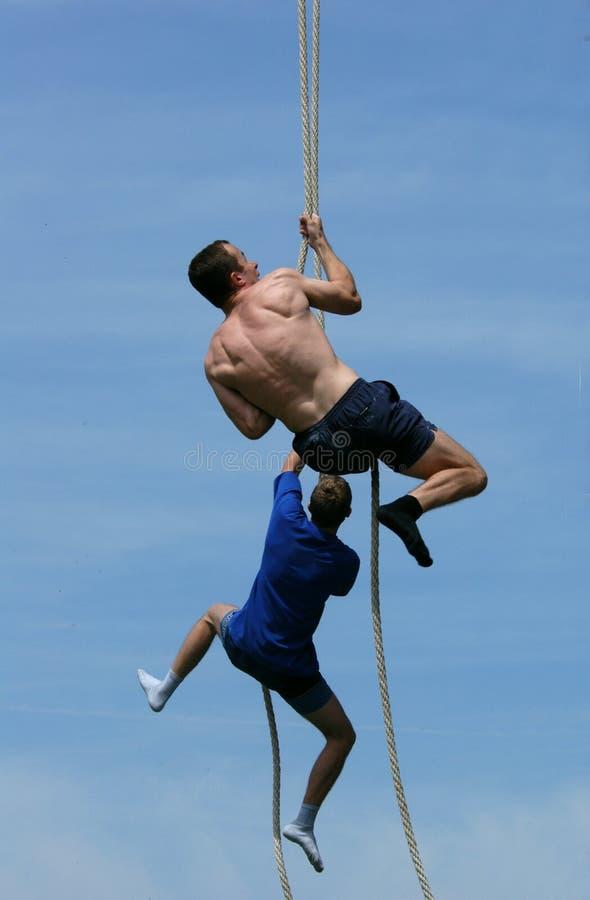 Athleten, die oben das Seil steigen stockfotos