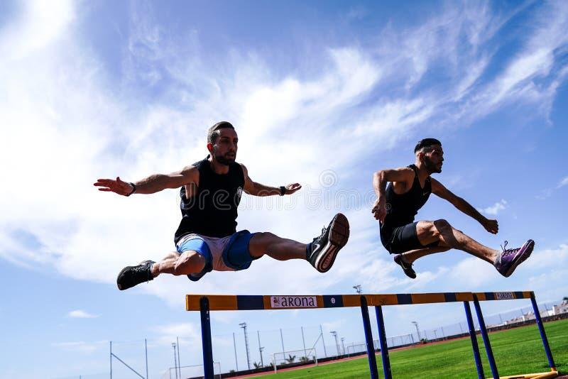 Athleten springt über eine Hürde während des Übens auf einer Laufbahn lizenzfreie stockfotos