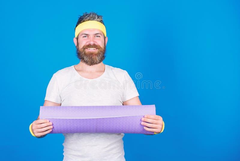 Athletenberufsyogatrainer motiviert f?r die Ausbildung Athletengriffeignungs-Matte des Mannes blauer Hintergrund der b?rtigen L?s stockfotografie
