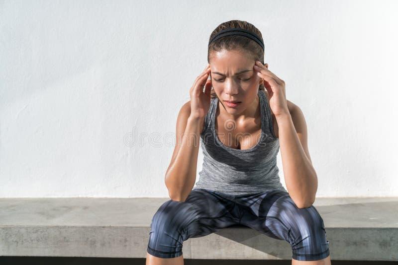 Athleteneignungsfrau mit den Kopfschmerzenmigräneschmerz stockbild