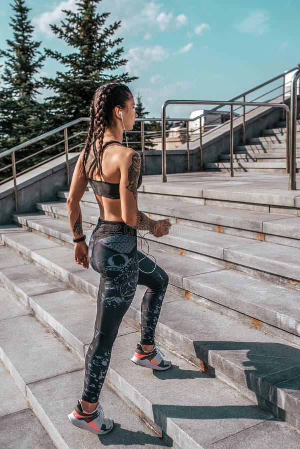 Athletenfrau geht Trainings-Sommerstadt des Sports hei?e Kopfh?rer rufen, Online-Bewerbungs-Musiksoziale netzwerke an Konzept stockfotos