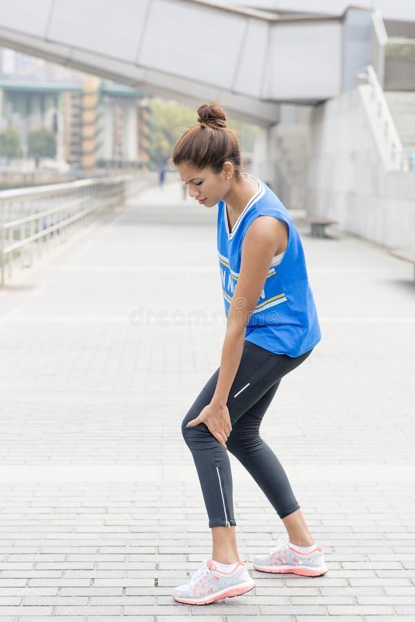Athletenfrau hat die Beinschmerz nach Übung lizenzfreies stockbild