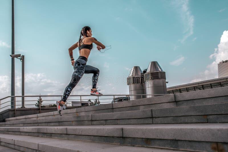 Athletenfrau l?sst den Sprungssport laufen, der Trainingssommerstadt r?ttelt Kopfh?rer telefonieren Frischluft der Konzepteignung lizenzfreie stockbilder