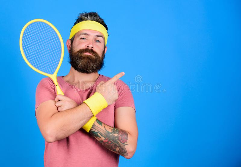 Athletengriff-Tennisschläger in der Hand auf blauem Hintergrund Tennissportanzeige Tennisvereinkonzept Mann bärtig lizenzfreies stockfoto