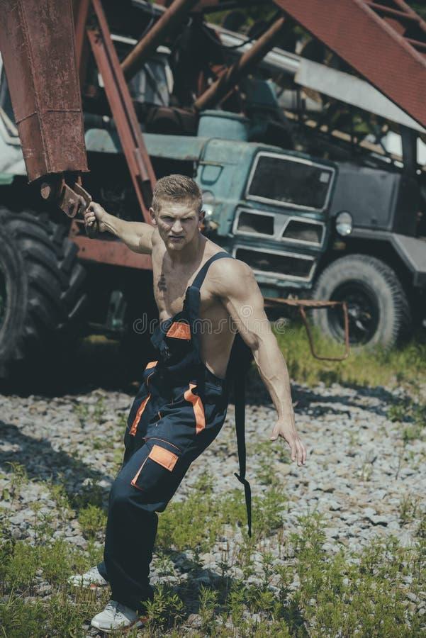 Athletenkonzept Schwerer Eisenkran des Athletenzuges Starker Athlet auf Baustelle Energieathlet mit dem muskulösen Torso stockfoto