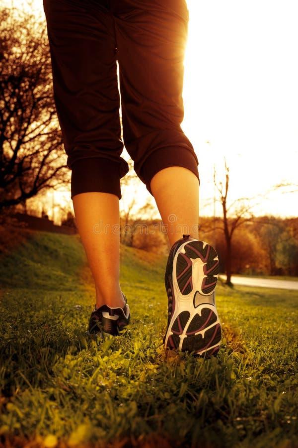Athletenläuferfüße, die auf Gras laufen stockbild