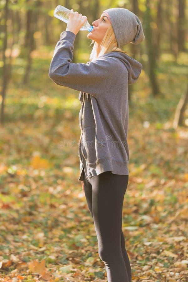 Athletenmädchen, das eine Pause während des Laufs zum Hydrat macht lizenzfreie stockfotografie