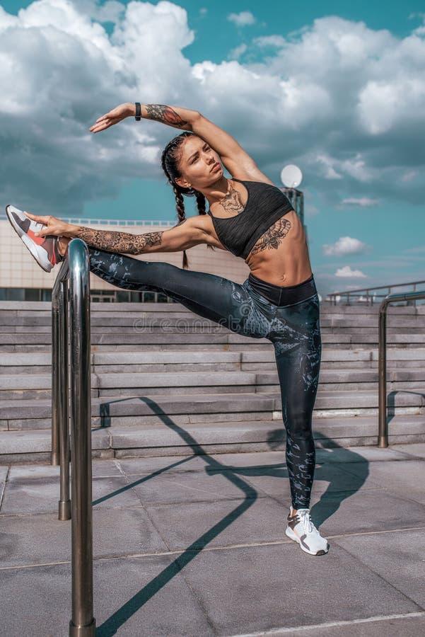 Athletenm?dchen, welches das Ausdehnen in Sommer in der Stadt, ?bendes Yoga tut Sportkleidungsgamaschen-Spitzenturnschuhe, Frau D stockbild