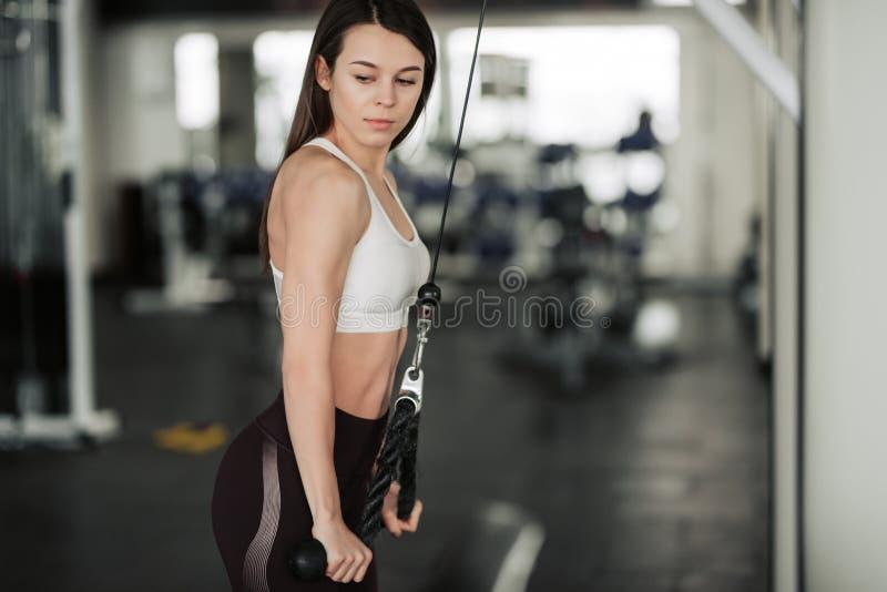 Athletenm?dchen in der Sportkleidung ihre Arme und Schultern mit ?bungsmaschine in der Turnhalle ausarbeitend und ausbildend stockfotografie