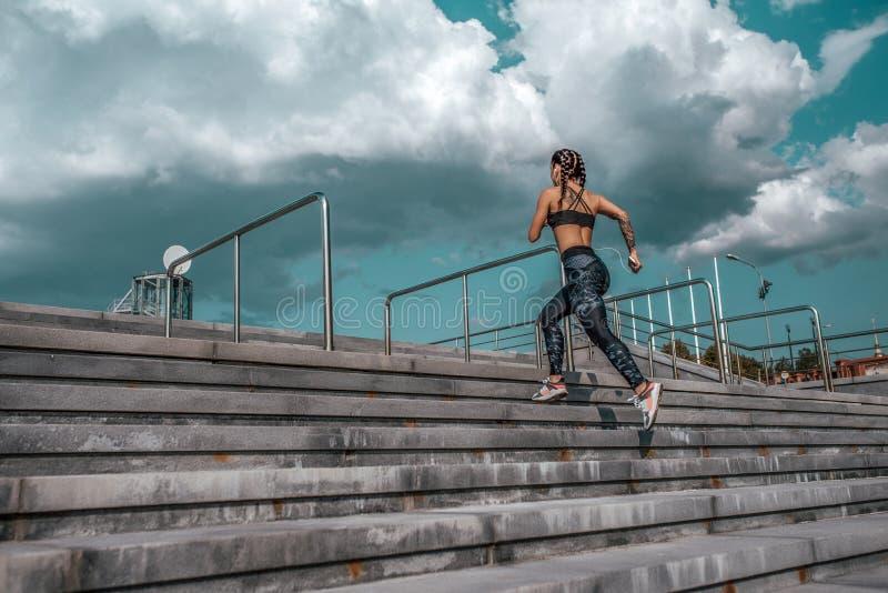 Athletenm?dchen l?sst den Sprungssport laufen, der Trainingssommerstadt r?ttelt Kopfh?rer telefonieren Frischluft der Konzepteign lizenzfreie stockfotos