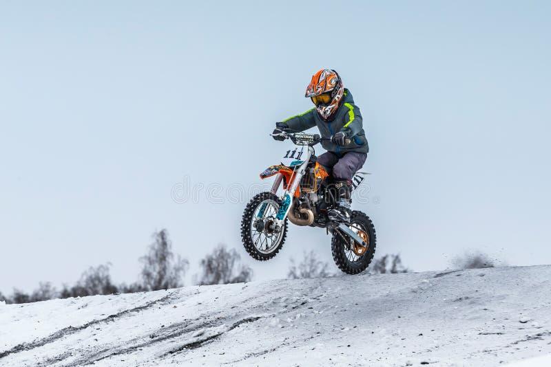 Athletenmotorrad des kleinen Jungen, das über Hügel auf Motocross springt stockfoto