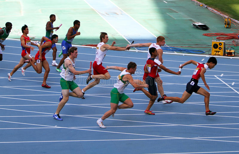 Athletes on the 4 x 100 meters relay race stock images