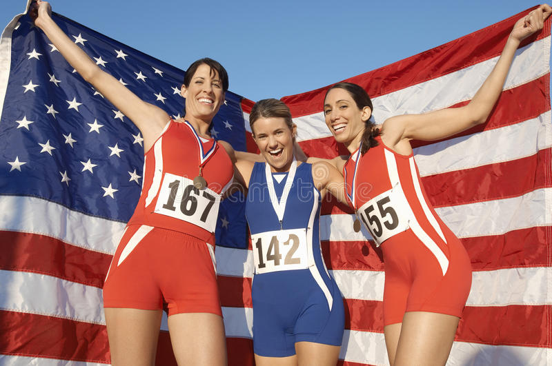 Athletes Celebrating With Medals And American Flag. Portrait of happy female athletes celebrating with medals and American flag against the sky stock photo