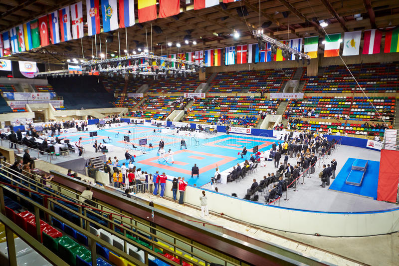 Athletes, judges, spectators at Small sports arena stock photo