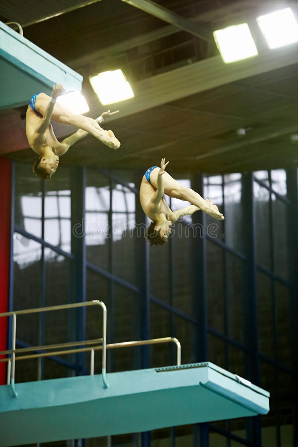 Athletes jump from tower at competitions stock image