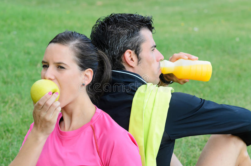 Athletes Nutrition. Couple of athletes taking a break, eating an apple and drinking isotonic drink royalty free stock image
