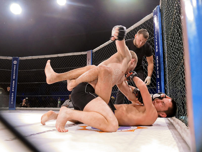 Athletes in the Octagonal ring for fights extreme Sport mixed martial arts competition tournament MMA MAXMIX. Odessa, Ukraine - 24 November 2015: Athletes in the stock photography