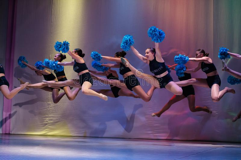 Athletes perform on stage, young cheerleaders perform at the cheerleading championship, girls in a jump, girls are holding pompons stock images