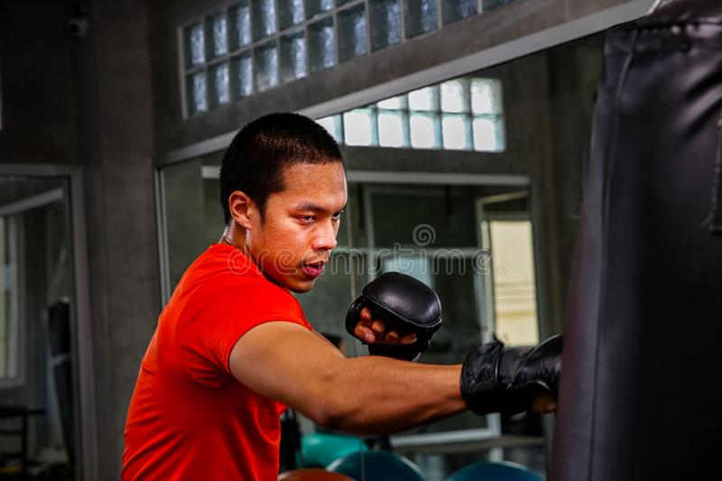 Athletes are punching in the gym. Male action of a boxing fighter training on a punching bag in the gym. Man boxer training is. Exercising with a punching bag royalty free stock photos