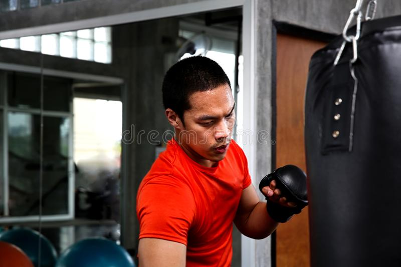 Athletes are punching in the gym. Male action of a boxing fighter training on a punching bag in the gym. Man boxer training is. Exercising with a punching bag stock images