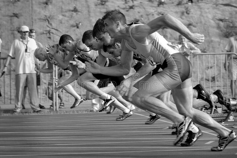 Athletes Running on Track and Field Oval in Grayscale Photography royalty free stock images