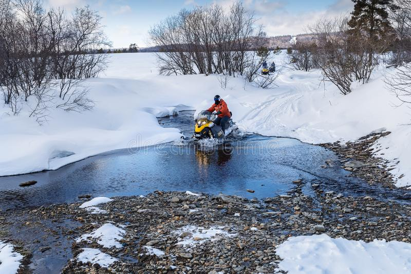 Athletes on a snowmobile. Forwarded across a river in the mountains of the Urals royalty free stock photos