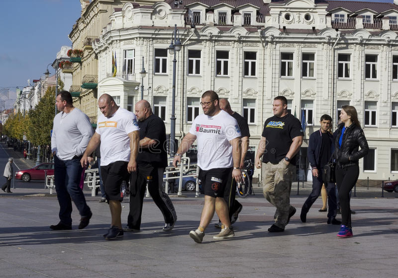 Athletes walk on the city. VILNIUS, LITHUANIA - OCTOBER 05, 2014: Big athletes walk on the small city. Prize winners of the European championship of athletes stock images