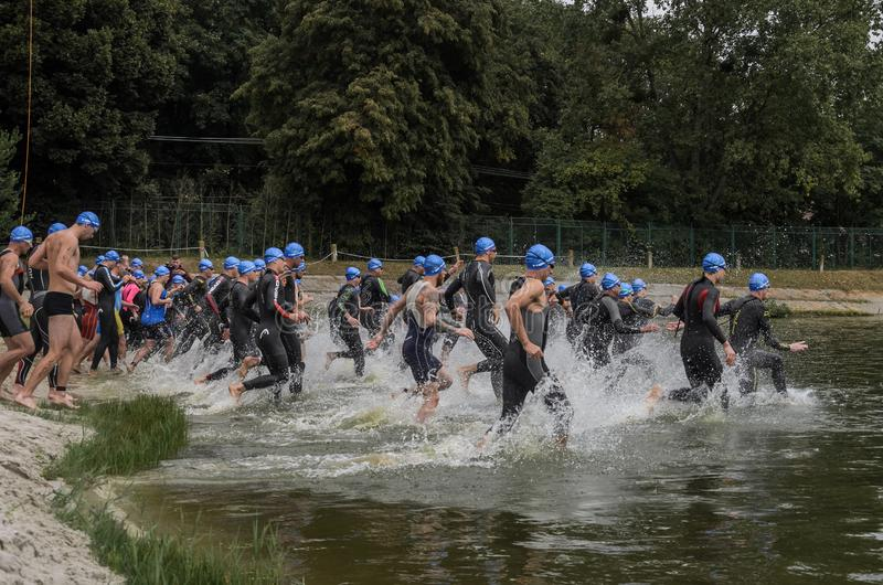 UKRAINE, LVIV - SEPTEMBER 2018: Athletes in wetsuits at the start run into the water for a swim in the triathlon competition. Athletes in wetsuits at the start royalty free stock photography