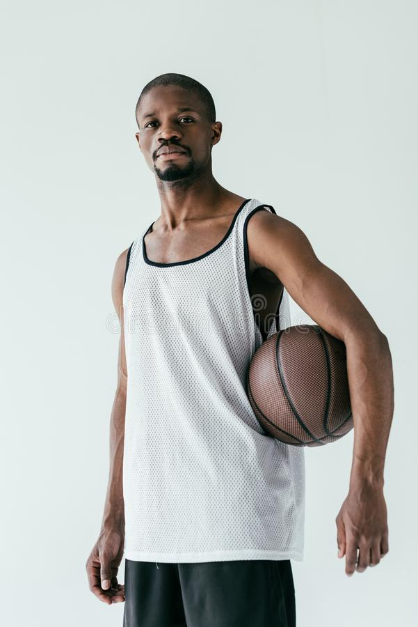 Athletic african american basketball player in sportswear with ball. Isolated on white stock photo