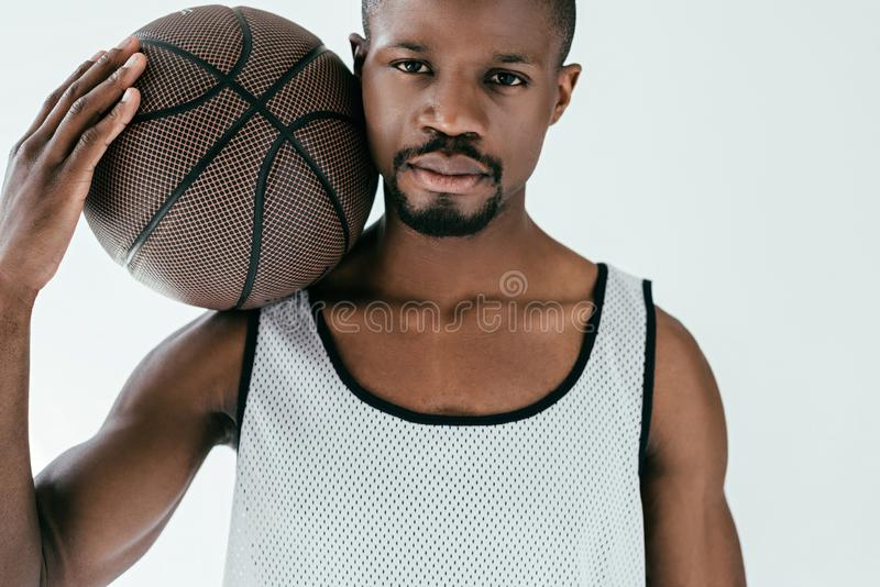 Athletic african american man with basketball ball. Isolated on white stock photo