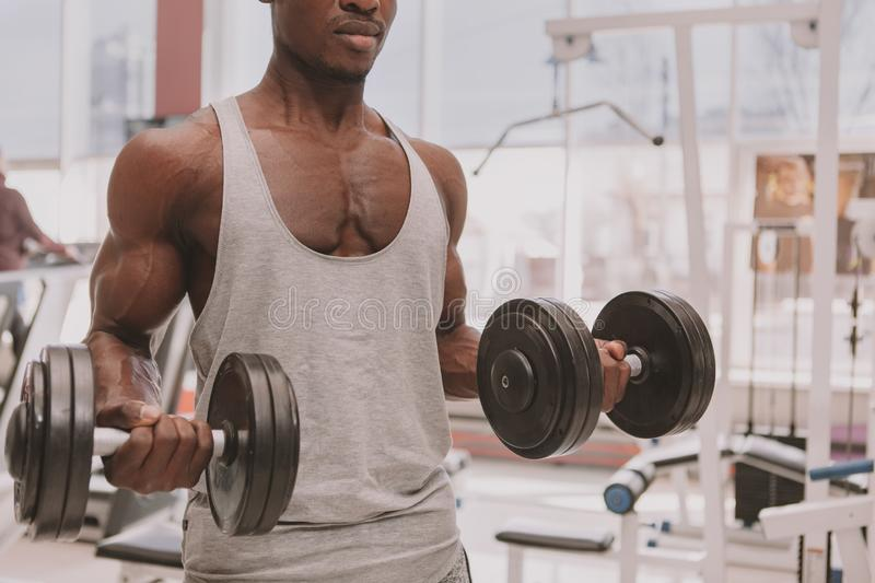 Athletic African man working out with dumbbells at the gym royalty free stock photos