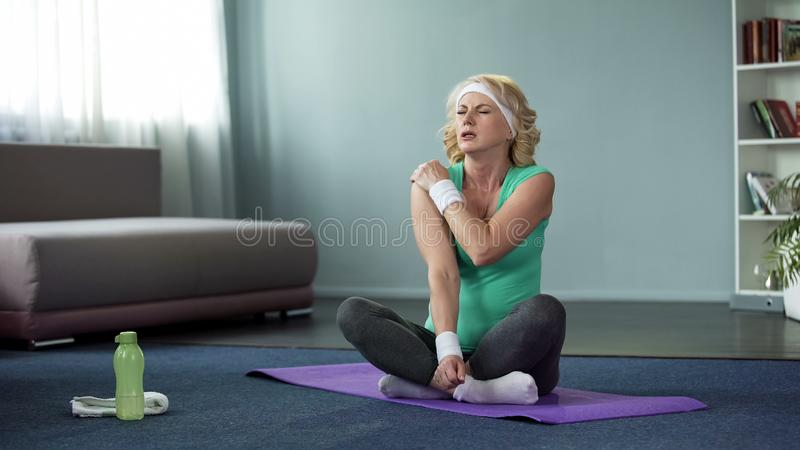Athletic aged lady touching her shoulder, sitting mat, sport injury, muscle pain royalty free stock photography